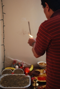S's Dad plants the jamara in the aluminum pans and starts the puja