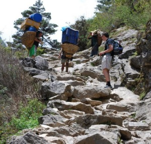 Passing porters carrying heavy loads up the mountain trail...