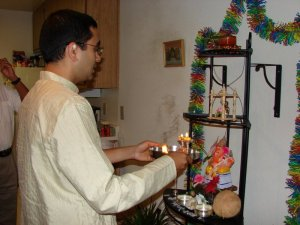 Example of a man doing aarti for puja with the platter of incense and candle